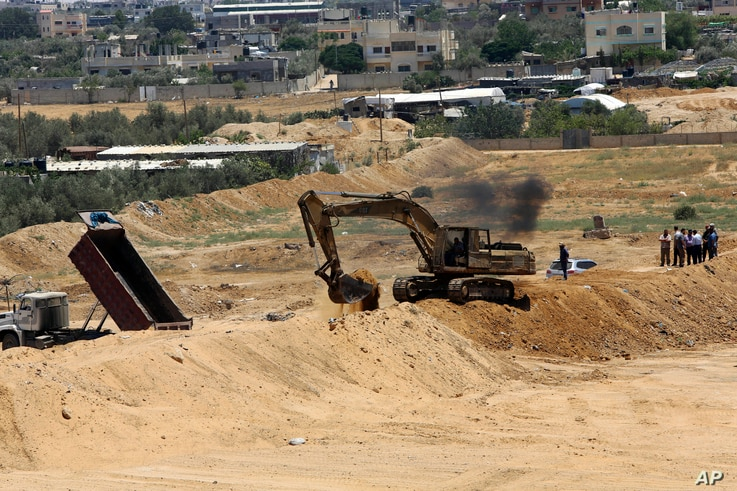 FILE - A backhoe removes sand barriers to create a buffer zone along the Egyptian border with the Gaza strip, near entrances to smuggling tunnels, background, in Rafah, June 28, 2017.