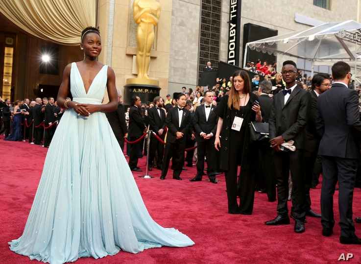 """Lupita Nyong'o arrives at the Oscars in Los Angeles, March 2, 2014. Nyong'o, wearing a light blue Prada gown, won the Oscar for best supporting actress for her role in """"12 Years a Slave."""""""