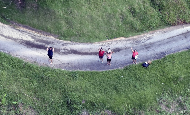 This photo made available by the U.S. Coast Guard shows residents near Utado Puerto Rico, waiting for supplies to be dropped from the air, Oct. 3, 2017.
