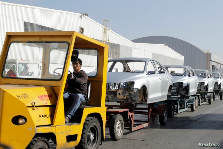 FILE - A worker transports car chassis at the Volkswagen plant in Puebla, Mexico, March 9, 2015.