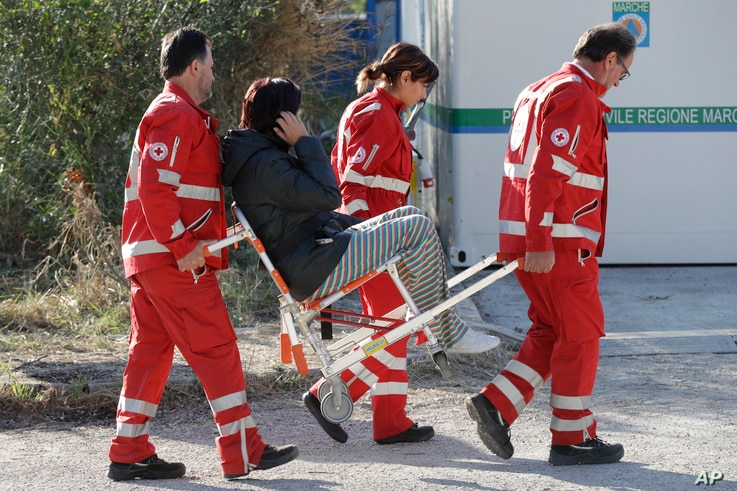 An earthquake survivor is carried by Red Cross staff in a tent camp set up as a temporary shelter following an earthquake in Pescara Del Tronto, Italy, Aug. 26, 2016.