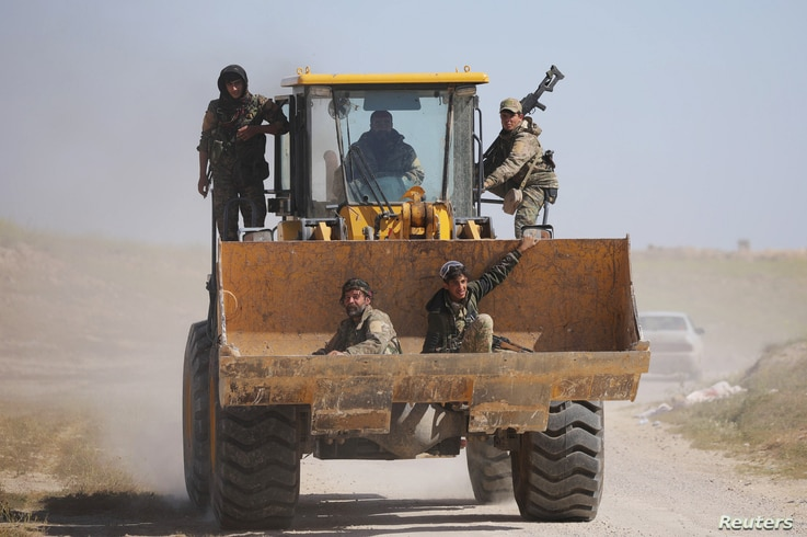 Fighters from the Syrian Democratic Forces sit in the bucket of an excavator in the village of Baghuz, Deir el-Zour province, Syria, March 20, 2019.