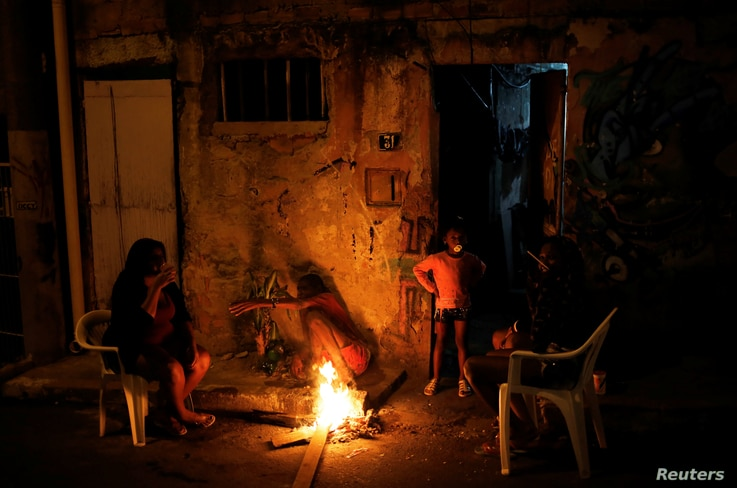 A family is pictured at the entrance of their house at a slum, or favela, in Rio de Janeiro, Brazil, June 26, 2016.