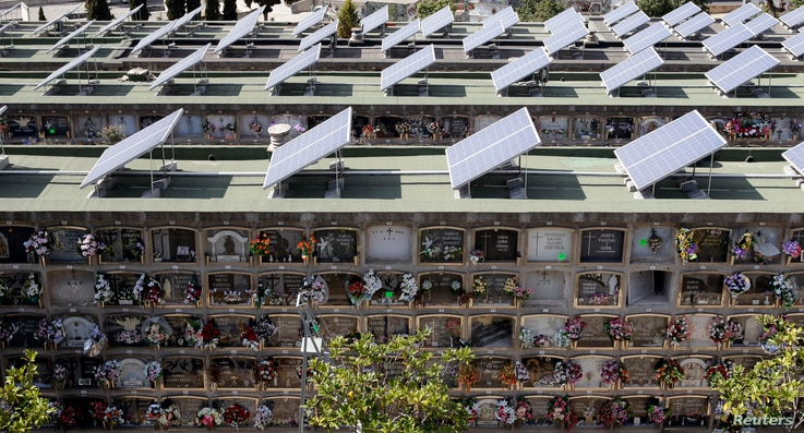 FILE - Solar panels fill the roofs of mausoleums in a cemetery in Santa Coloma de Gramanet, near Barcelona, Spain, March 28, 2011.