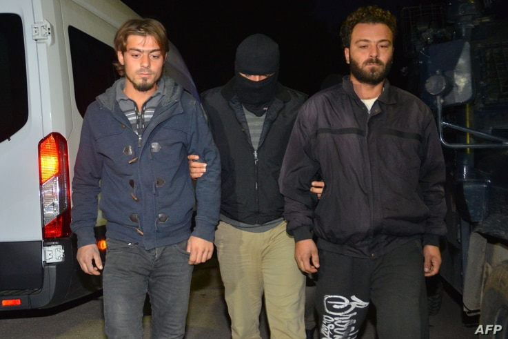 FILE - A masked Turkish special force police officer detains two men during a house raid to arrest suspected members of the Islamic State group, in Adana, on Nov. 10, 2017.