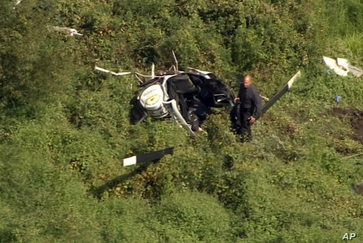 In this image from video provided by NBC10 Philadelphia, a first responder examines the wreckage of a helicopter in Lumberton, N.J., Sept. 8, 2017.