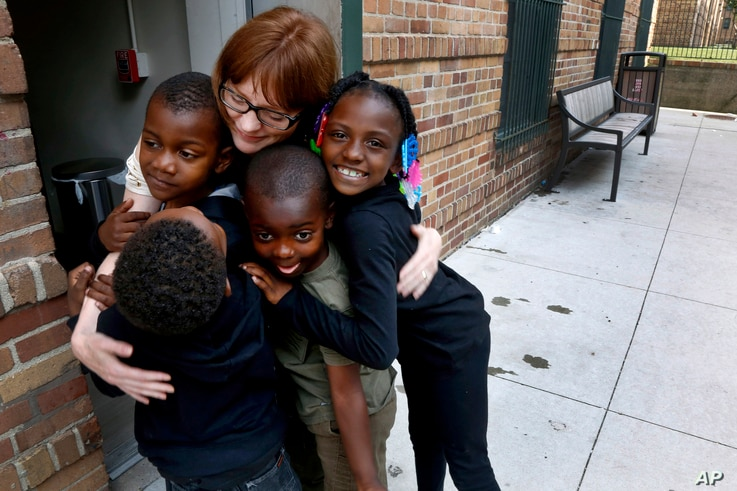 Charlie Branda, founder of Art on Sedgwick, hugs a few young residents of Marshall Field Garden Apartments in Chicago, June 25, 2018.