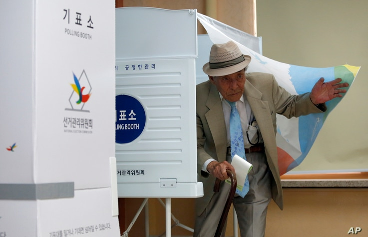 A local resident comes out of a polling booth to cast his ballot for parliamentary elections at a polling station in Seoul, South Korea, April 13, 2016.