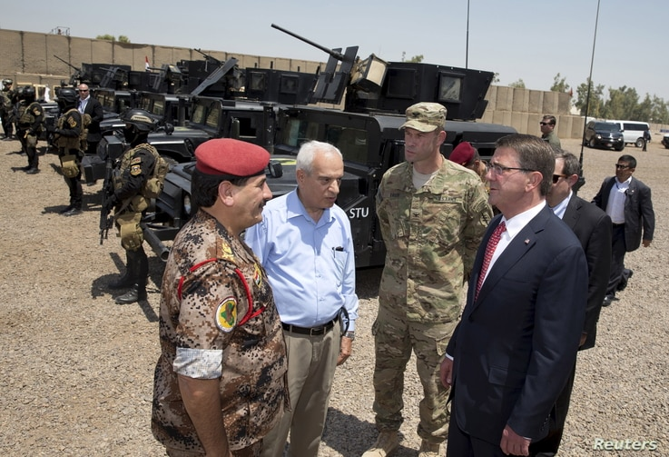 From right, U.S. Defense Secretary Ash Carter and Colonel Otto Liller, commander, 1st Special Forces Group Airborne greet Iraqi Major General Falah al Mohamedawi, left, at the Iraqi Counter Terrorism Service Academy in Baghdad, July 23, 2015.