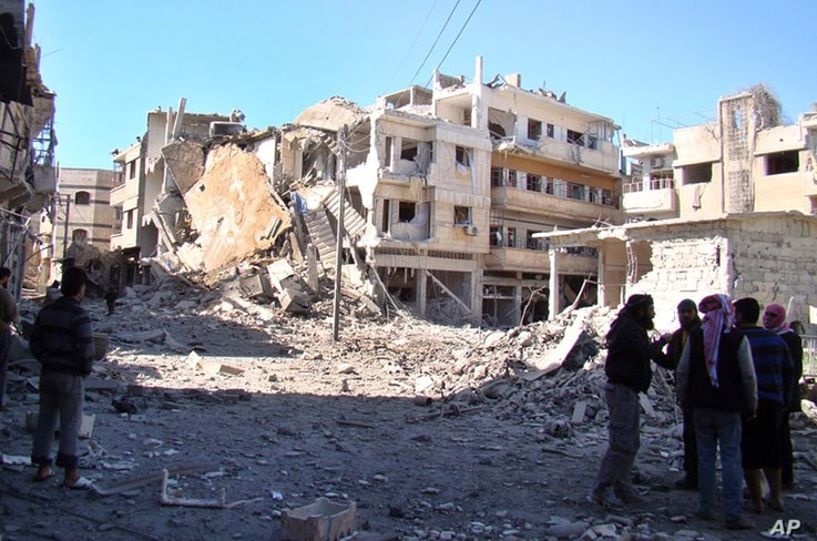 Syrian rebels stand in the rubble of damaged buildings due to government airstrikes in Homs, March 6, 2013.