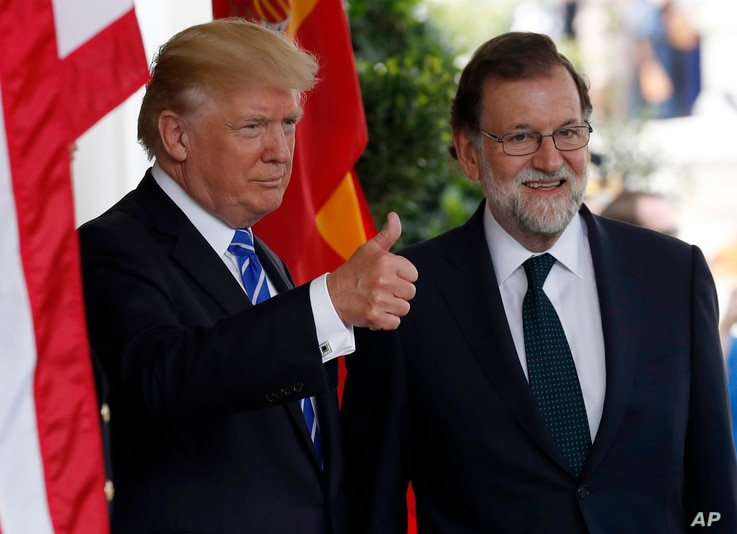 President Donald Trump gives thumbs up as he welcomes Spanish Prime Minister Mariano Rajoy at the White House, Sept. 26, 2017, in Washington.