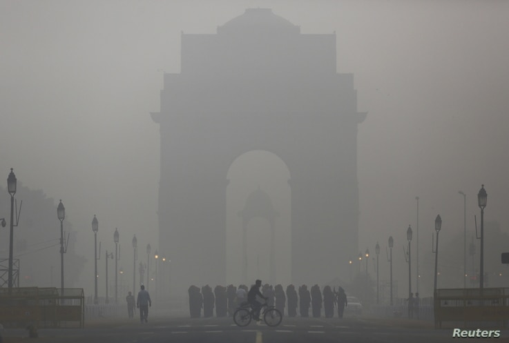 A man rides his bicycle next to Indian soldiers marching in front of India Gate on a smoggy morning in New Delhi, India, December 1, 2015.