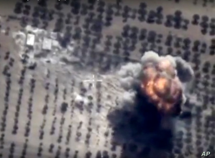 In this photo made from the footage taken from Russian Defense Ministry official web site on Friday, Oct. 16, 2015 showing a target hit during a Russian air raid in Syria. Russian Defense Ministry said the strike was performed by an Su-24M bomber in