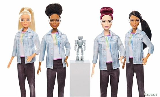 Four robotics engineer Barbies are seen flanked by a robot.