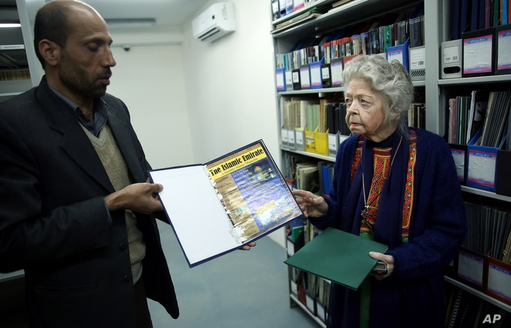 FILE - Nancy Hatch Dupree and her colleague show an archived paper of the Taliban regime during an interview with The Associated Press at the Afghanistan Center in Kabul University, Afghanistan, Dec. 9, 2014.