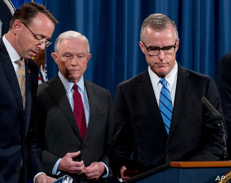 FILE - FBI Acting Director Andrew McCabe (R) accompanied by Attorney General Jeff Sessions (C), Deputy Attorney General Rod Rosenstein, takes the podium at a news conference at the Department of Justice, Washington, July 20, 2017.