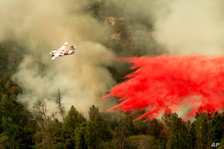 An air tanker drops retardant while fighting to stop the Ferguson Fire from reaching homes in the Darrah community of unincorporated Mariposa County, Calif., July 25, 2018.