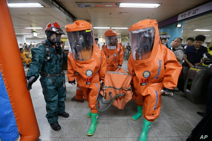 South Korean firefighters wearing protective gears move during an anti-terror drill as part of Ulchi Freedom Guardian exercise, at Yoido Subway Station in Seoul, South Korea, Aug. 23, 2016.