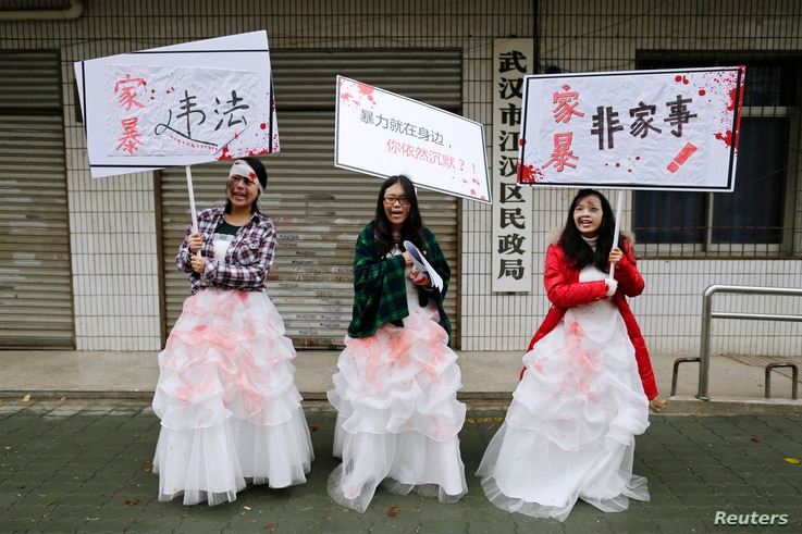 FILE - University students dressed as battered wives hold banners in front of an office of China's Civil Affairs department, where local people register for marriage, in protest of domestic violence, during the International Day for the Elimination o...