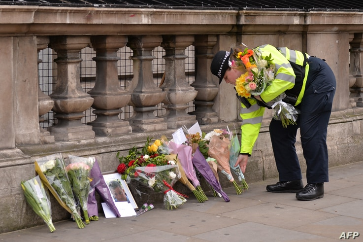 A police officer lays flowers on Whitehall around a photograph of police officer Keith Palmer who was killed in the March 22 terror attack in Westminster, near the Houses of the Parliament in central London on March 23, 2017.