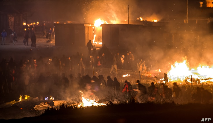 """Migrants evacuate as a huge fire blazes through the Grande-Synthe migrant camp outside the northern French city of Dunkirk late April 10, 2017, reducing it to """"a heap of ashes,"""" the regional chief said."""