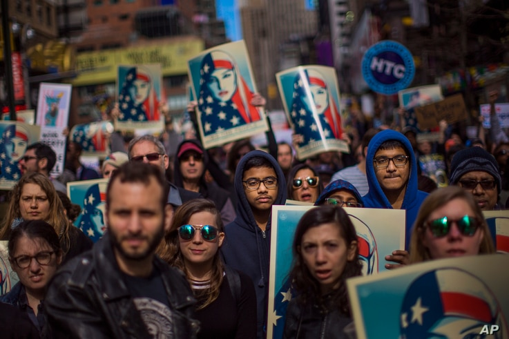 People carry posters during a rally in support of Muslim Americans and protest of President Donald Trump's immigration policies in Times Square, New York, Sunday, Feb. 19, 2017.