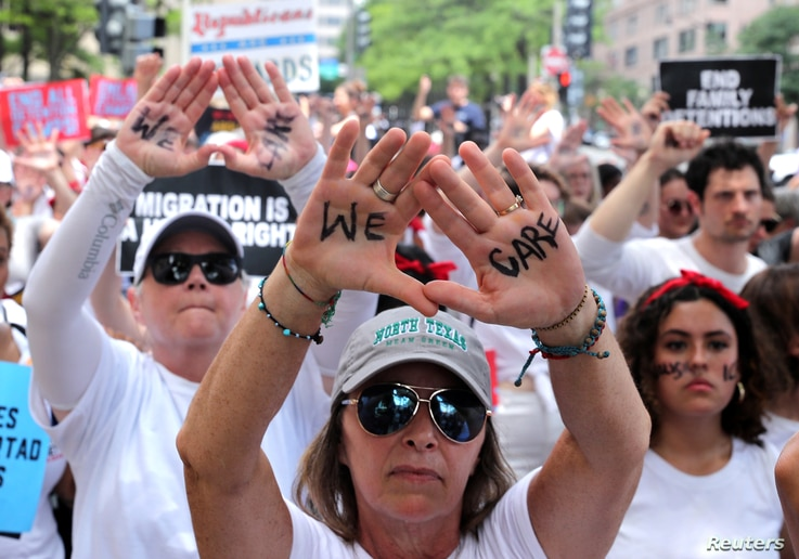 """Immigration activists rally as part of a march calling for """"an end to family detention"""" and in opposition to the immigration policies of the Trump administration, in Washington, June 28, 2018."""