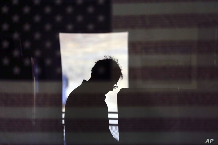 Hal Pigg is reflected in an image of a flag, as he casts his vote on Election Day in Jamul, California, Nov. 6, 2012.