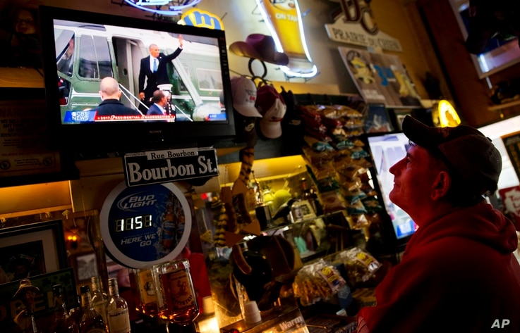 Robbo Coleman watches a live broadcast of former President Barack Obama waving goodbye during the inauguration of President Donald Trump at the Sawmill Saloon in Prairie du Chien, Wis., Jan. 20, 2017.