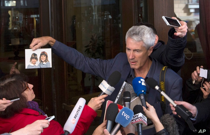 FILE - Anthony Foster, member of the Australian group of relatives and victims of priestly sex abuses, shows reporters a photo of his two daughters, who were both abused by the same priest and one of them later committed suicide, outside the Quirinal...