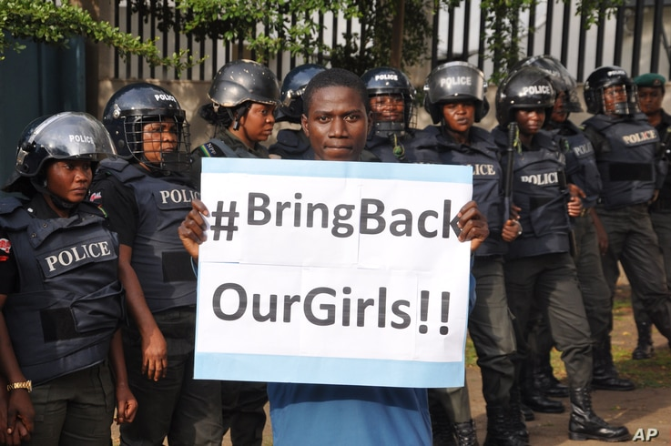 A man poses with a sign in front of police officers in riot gear during a demonstration calling on the government to rescue the kidnapped girls of the government secondary school in Chibok, in Abuja, Nigeria, Oct. 14, 2014.