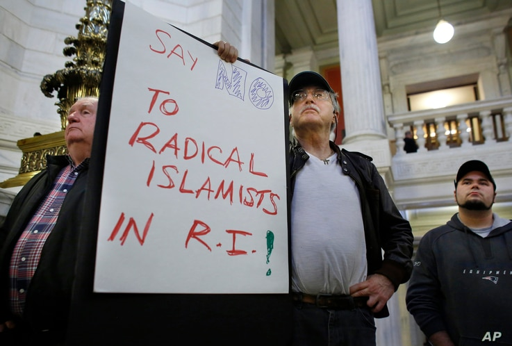 Howard Brown, of North Kingstown, R.I., center, displays a placard during a rally at the statehouse in Providence, R.I., held to demonstrate against allowing Syrian refugees to enter Rhode Island, Nov. 19, 2015.