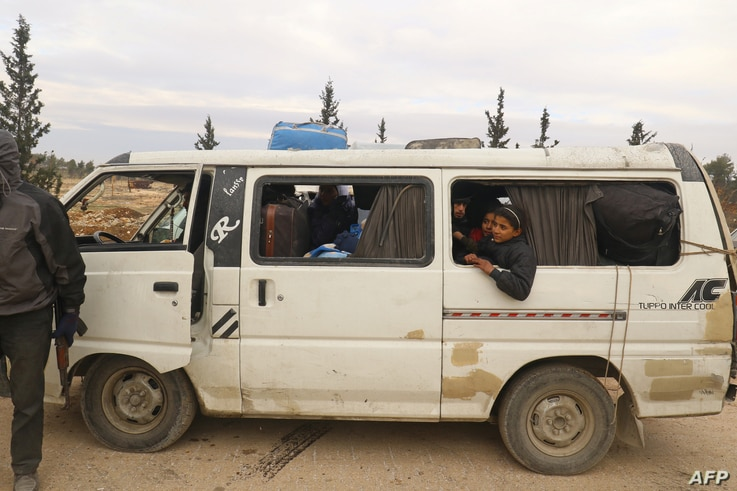 A rebel fighter stands near a bus transporting evacuees from rebel-held eastern Aleppo, upon their arrival to an area on the western edge of Aleppo city which is held by insurgents, in Syria Dec. 16, 2016.