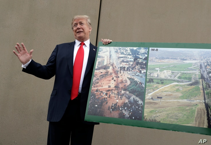 President Donald Trump holds a photo of the border area as he reviews border wall prototypes, March 13, 2018, in San Diego.