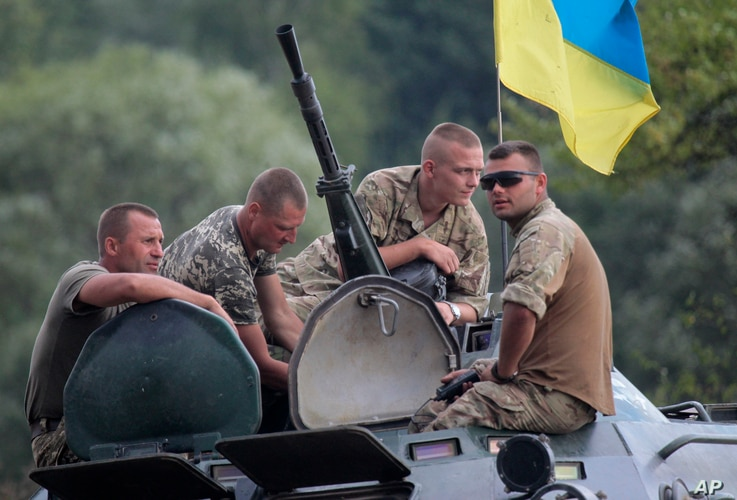 Ukrainian soldiers atop an APC watch training exercises under the supervision of British instructors on the military base outside Zhitomir, Ukraine, Aug. 11, 2015.
