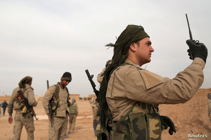 FILE - A Syrian Democratic Forces (SDF) fighter carries a walkie talkie as he stands with his fellow fighters during an offensive against Islamic State militants in northern Raqqa province, Syria February 8, 2017.