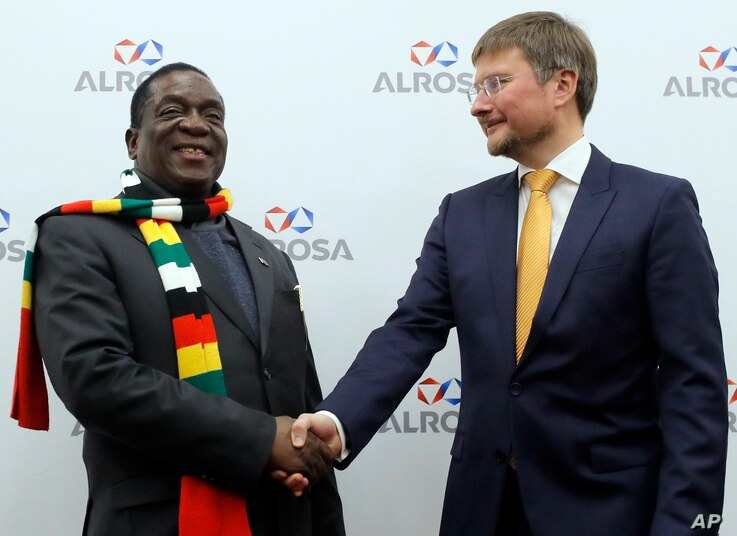 Zimbabwe's President Emmerson Dambudzo Mnangagwa, left, and CEO of of the Alrosa diamond mining company Sergey Ivanov shake hands during their meeting in Moscow, Jan. 14, 2019.