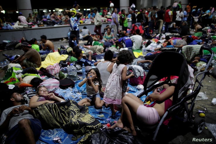 Migrants, part of a caravan of thousands of migrants from Central America en route to the United States, rest along the sidewalks of Tapachula city center, Mexico, Oct. 21, 2018.