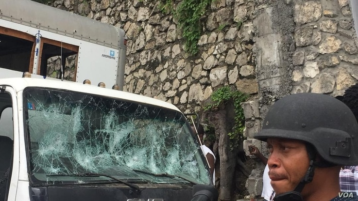 At one point in the protest, demonstrators threw rocks, damaging cars parked on the road, in Port-au-Prince, Haiti, March 29. 2019.