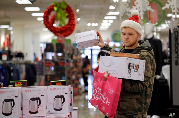 Joey Ellis adds to his armful of items while shopping for deals at a J.C. Penney store, Nov. 24, 2017, in Seattle. Black Friday has morphed from a single day into a whole season of deals, so shoppers may feel less need to be out.