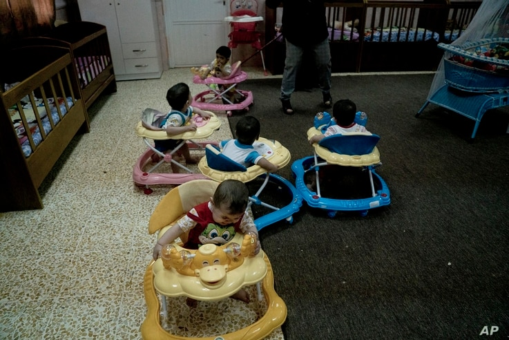 FILE - Babies toddle around in walkers at the state-run al-Zuhour Orphanage in Mosul, Iraq, Aug. 19, 2018. Orphanages are where wars play out: children abandoned in the chaos of battle, children born of rape and sexual slavery, babies left behind in ...