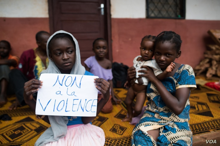 "A young displaced Muslim girl holds a sign saying ""No to Violence"" at a displaced persons site, the Catholic church in Bangassou, Central African Republic."