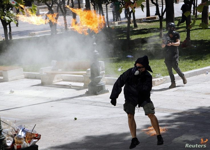 A demonstrator throws a molotov cocktail to riot police officers near Syntagma square during a 24-hour labour strike in Athens September 26, 2012. Greek police fired teargas at hooded youths hurling petrol bombs and stones as tens of thousands took t...