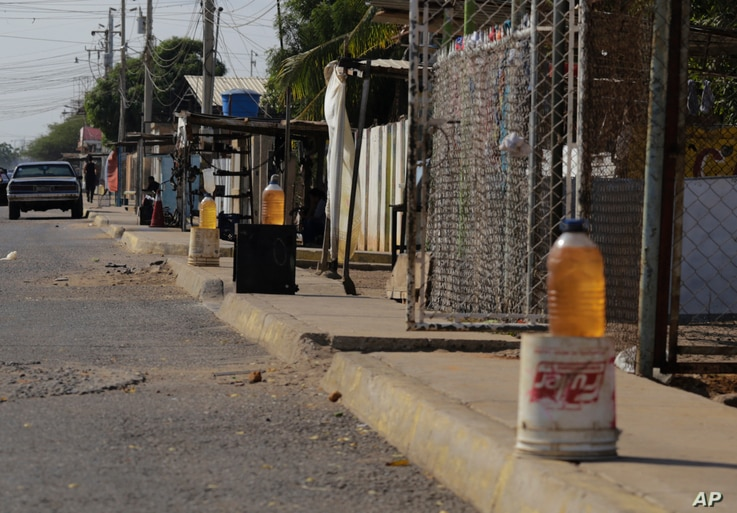 In this Jan. 30, 2019 photo, bottles of black market gasoline sit for sale on a sidewalk in Maracaibo, Venezuela.