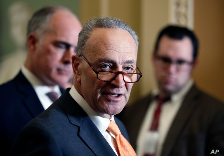 Senate Minority Leader Chuck Schumer of N.Y., center, accompanied by Sen. Bob Casey, D-Pa., at left, speaks on Capitol Hill, Feb. 6, 2018 in Washington.