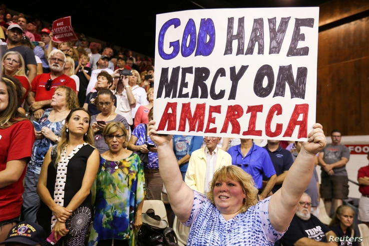 A supporter holds up a sign as Republican presidential nominee Donald Trump speaks during a campaign rally in Sarasota, Florida, U.S. Nov. 7, 2016.