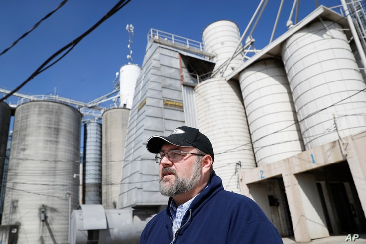 FILE - Matt Aultman, a grain salesman and feed nutritionist with Keller Grain & Feed, Inc., speaks beside grain and soybean silos at their facilities in Greenville, Ohio, April 5, 2018. Rural America is struggling under a cloud of uncertainty as the ...