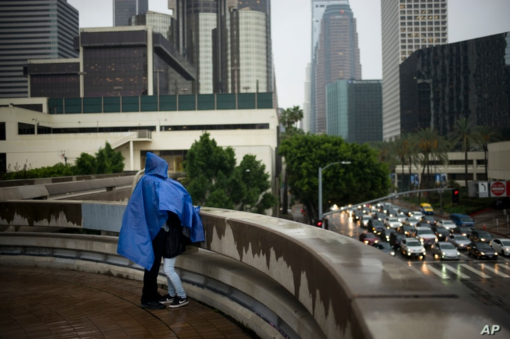 Jerry Rodriguez, left, shares a rain poncho with his girlfriend, Lilyana Del Villar, Feb. 10, 2017, in downtown Los Angeles. A strong storm is forecast to hit Southern California this weekend.
