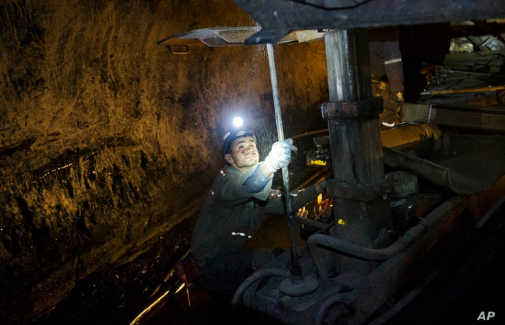"""FILE - In this Oct. 6, 2015 photo, a miner works underground in the Sewell """"R"""" coal mine in Yukon, W.Va."""