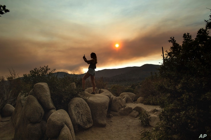 Mara Schumann photographs a plume of smoke from the Ferguson Fire in Yosemite National Park, Calif., July 24, 2018. Parts of the park, including Yosemite Valley, closed as firefighters worked to stop the blaze.